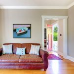 gray walls old leather couch open door wall art