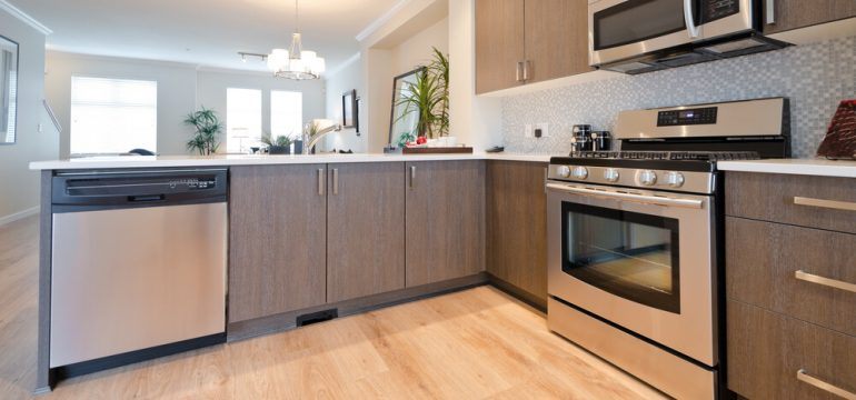 modern kitchen stainless steel appliances wood grain flooring
