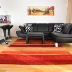 modern living room red accents black couch wood floor