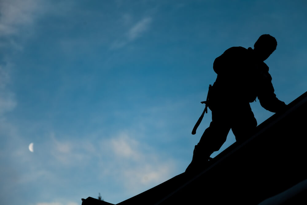 roofer on roof in silhouette