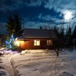 small house in the snow with sky and moon night