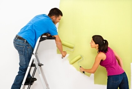 Attractive young adult couple painting interior wall of house.