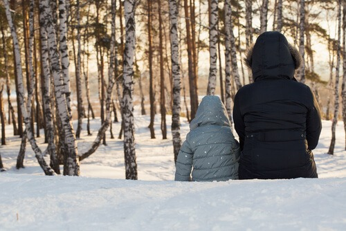 mother and child sitting snow birch trees