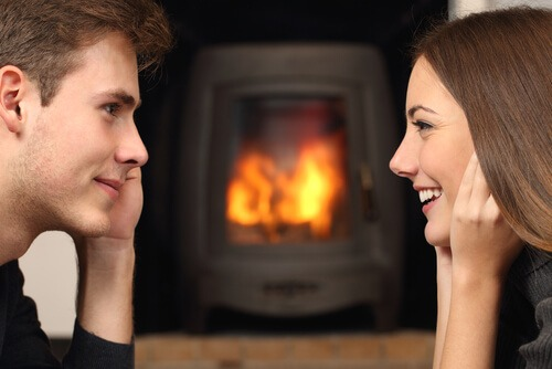 couple looking at each other smiling profile fireplace