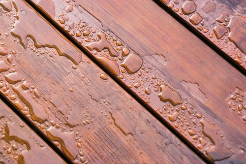 Pooled water on finished deck with woodgrain