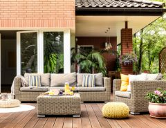 Yellow pouf next to a rattan armchair