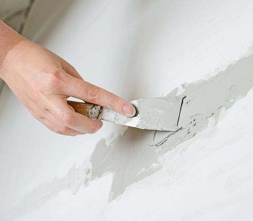 hand-repairs-wall-with-spackling-paste