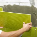 man-installing-green-wall-tile