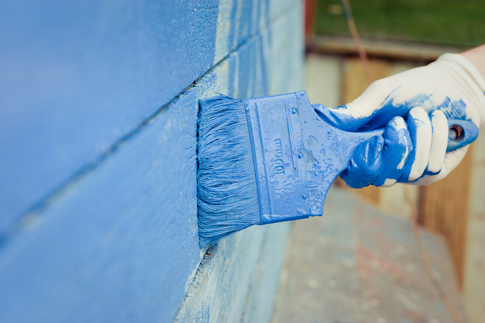 painting-siding-blue-with-paint-brush